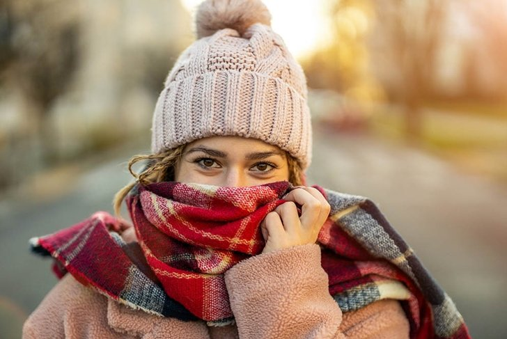 Beautiful young woman feeling cold in winter