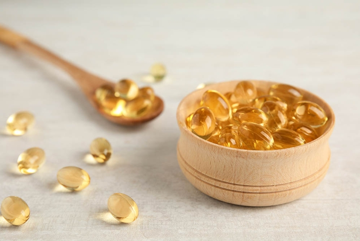Bowl and spoon with cod liver oil pills on light background