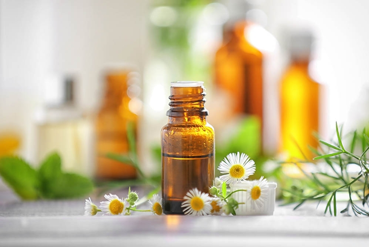 Bottle with essential oil and chamomile flowers on wooden table