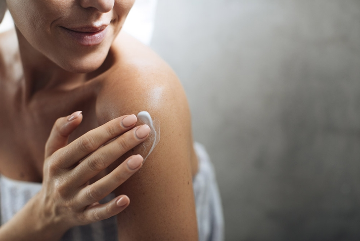 woman putting lotion on arm