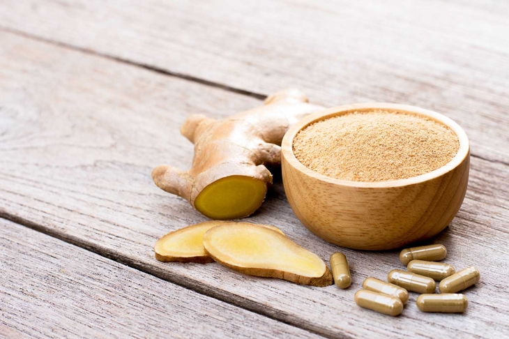 Fresh ginger slice and powder capsules with ginger ground in wooden bowl isolated on wood table background. Herbal medicine plant and supplement concept.