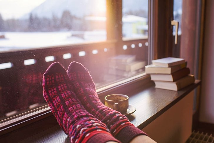 Feet in woollen socks by the Alps mountains view. Woman relaxes by mountain view with a cup of hot drink. Close up on feet. Winter and Christmas holidays concept.