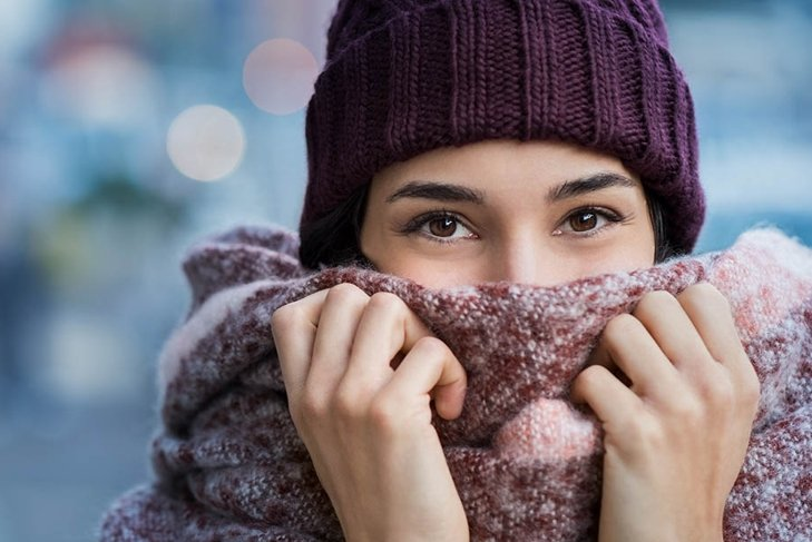 Winter portrait of young beautiful woman covering face with woolen scarf. Closeup of happy girl feeling cold outdoor in the city. Young woman holding scarf and looking at camera.