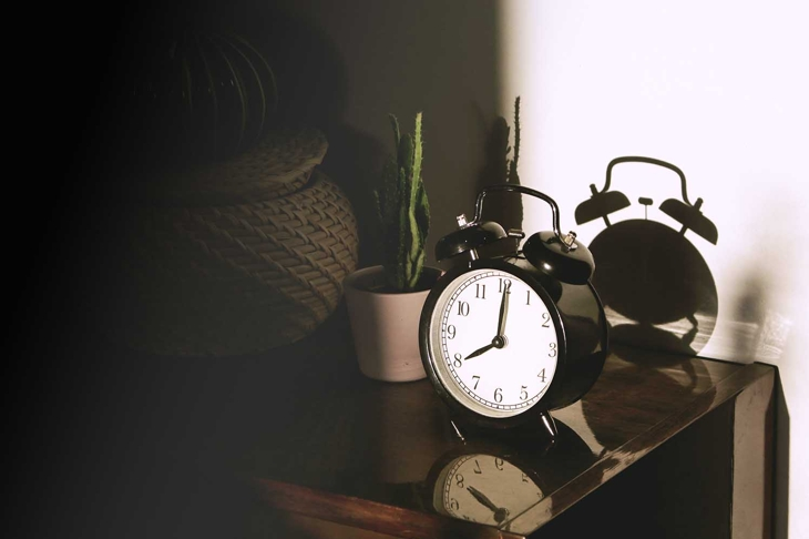 Black retro vintage alarm watch clock on a wooden bedside table with reflection in a polished surface in the rays of the setting sun with hard shadows