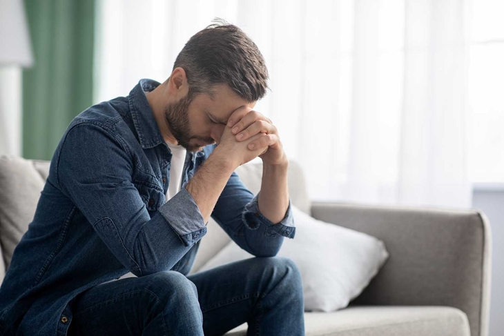 Depressed middle-aged man sitting on couch in living room, leaning on his hands, having financial troubles during quarantine or suffering from loneliness, copy space, home interior