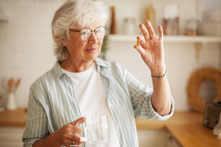 Beautiful mature sixty year old female in stylish eyeglasses holding mug and omega 3 supplement capsule, going to take vitamin after meal. Senior gray haired woman taking fish oil pill with water