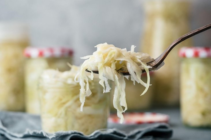 Sauerkraut on fork and unfocused glass jars with kraut. Pickling or fermented cabbage at table in home. Homemade sauerkraut with copy space for text