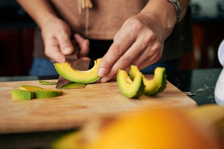 Hands peeling cut avocado slices on wooden board