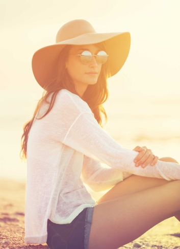 Woman sits in the sun and shows how you can be sun safe using natural sun lotion