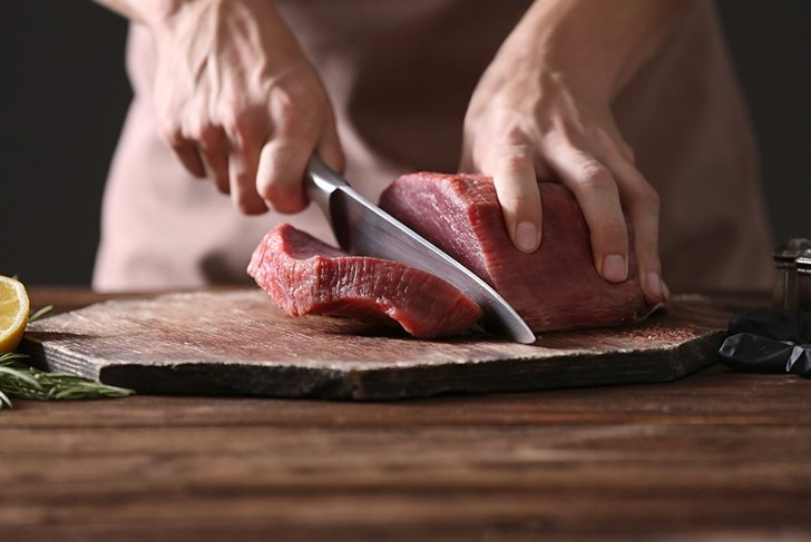 butcher cutting pork meat