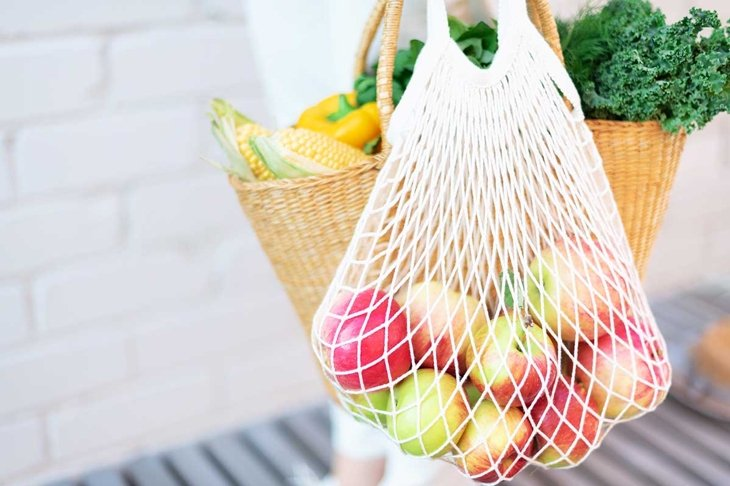 Zero waste concept with copy space. Woman holding straw basket and reusable mesh shopping bag withapples, vegetables, white brick background. Eco friendly mesh shopper. Copy space.