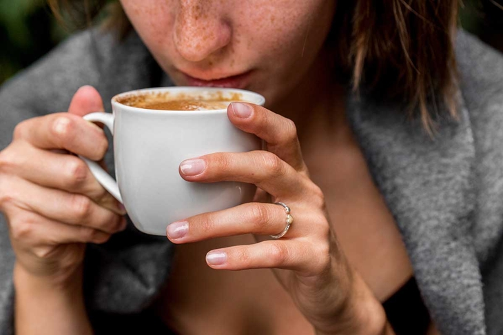 Pretty girl wrapped in blanket drinks coffee
