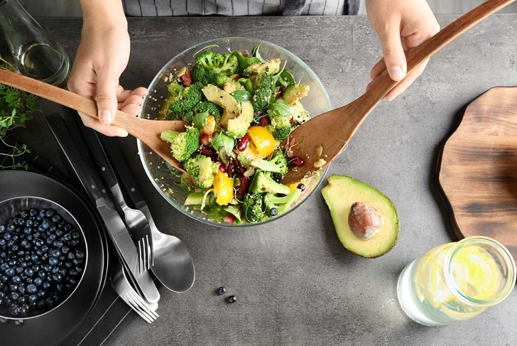 Woman mixing delicious superfood salad ingredients with wooden spoons in kitchen
