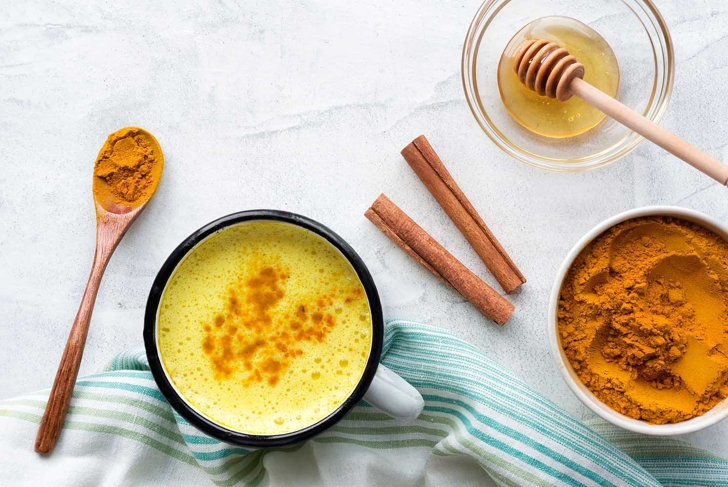 Turmeric latte, Cooking Golden Milk On Kitchen. Hot healthy drink. Top view.