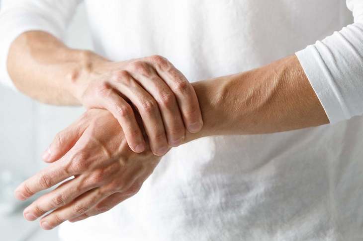 Closeup of male arms holding his painful wrist caused by prolonged work on the computer, laptop. Carpal tunnel syndrome, arthritis, neurological disease concept. Numbness of the hand