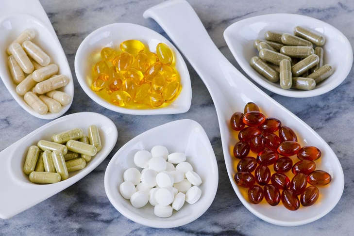 Variety of dietary supplements, including capsules of Garlic, Evening Primrose Oil; Artichoke Leaf; Olive Leaf; Magnesium and Omega 3 Fish Oil.Selective focus. Taken in daylight.