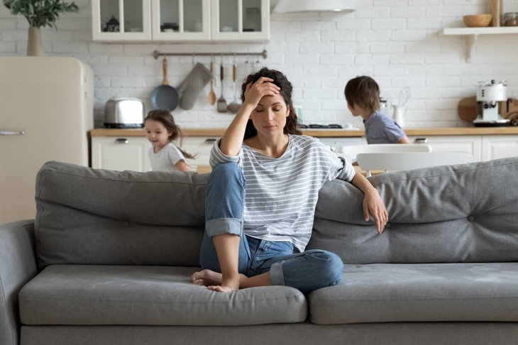 Young tired single mother suffers from headache closed eyes touch forehead sitting on couch while her daughter and son running around her and shouting, female babysitter feels exhausted by noisy kids