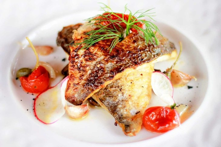 Grilled red snapper with burnt butter, capers, tomato and lemon sauce. Fresh seafood dish in restaurant, Phuket, Thailand.