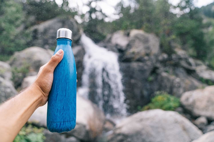 Sustainable and reusable water bottle. Hand holding a blue Eco Friendly Water Bottle. Goodbye to single use plastic bottles. Plastic free and zero waste. Sustainable life.