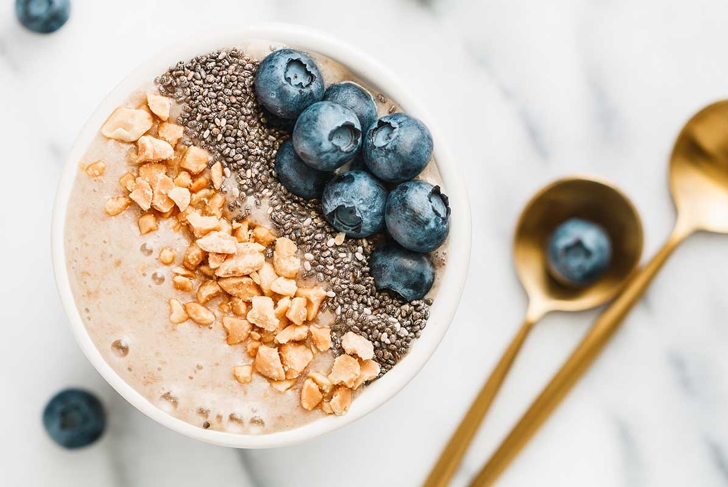 Top view of a smoothie bowl with fresh ripe blueberry, nuts, chia, banana and soya milk over white background. The concept of healthy eating and lifestyle.