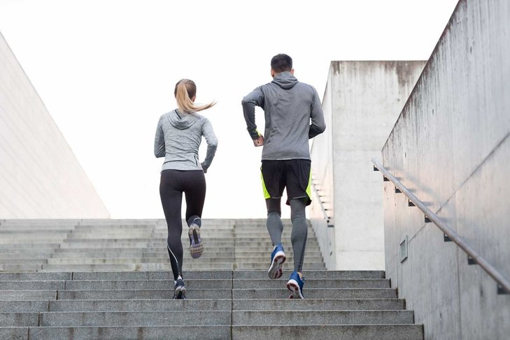 fitness, sport, people, exercising and lifestyle concept - couple running upstairs on city stairs