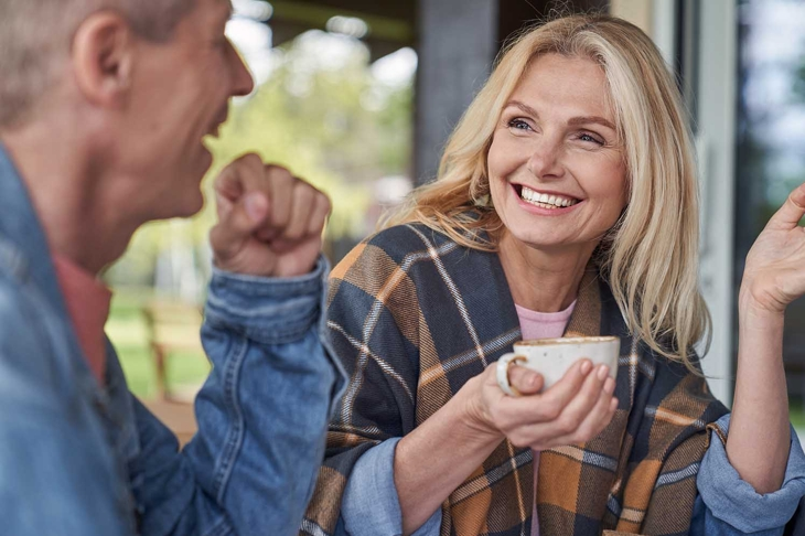 Cheerful mature lady is communicating with husband while relaxing with mugs of tea in green countryside