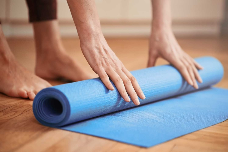 Close up of mature woman folding blue yoga or fitness mat before or after working out at home in living room. Healthy life in covid-19 time lockdown. Focus on hand. Little bit of film grain