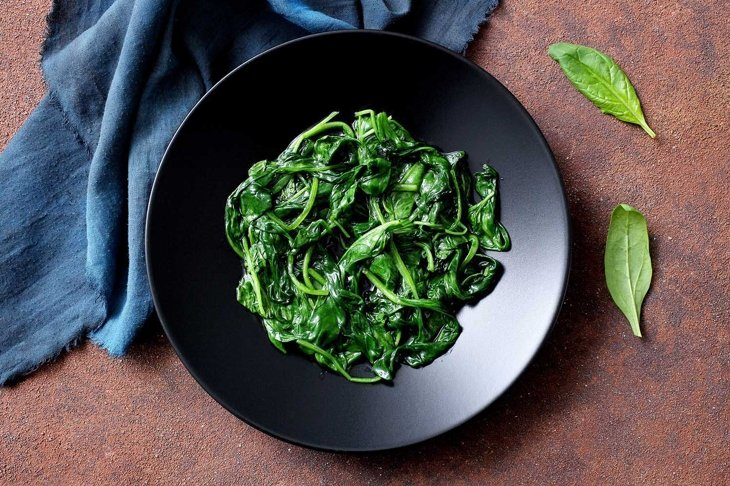vegetarian food cooked spinach in black dish