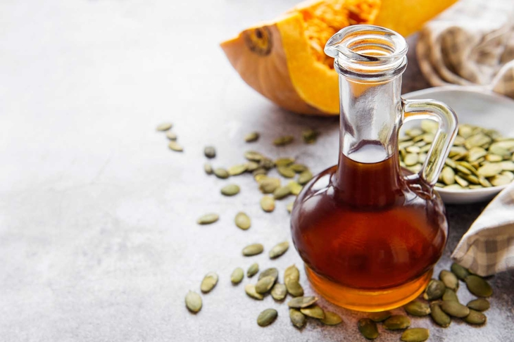 Bottle with pumpkin seed oil on gray concrete background