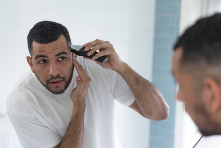 Mixed race male trimming and grooming in his bathroom