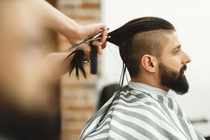 Man's hands doing a haircut for man with dark long hair and beard at barber shop, close up portrait, copy space.