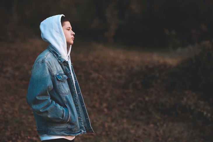 Handsome teen boy wearing denim jacket and white hoodie standing outdoors over nature autumn background. Teenagerhood.