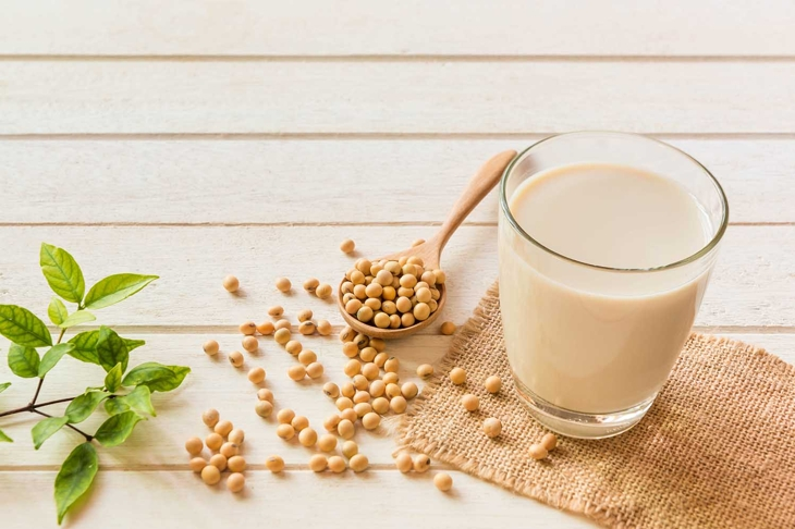 Soy milk in glass and soy bean on spoon it on white table background,healthy concept.