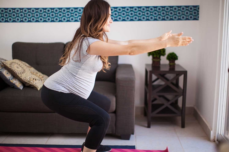 Profile view of a pregnant brunette working out and doing squats at home