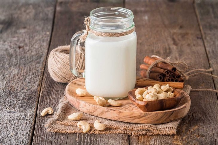 Cashew nut vegan milk non dairy in a glass jar with cashew nuts on wooden background