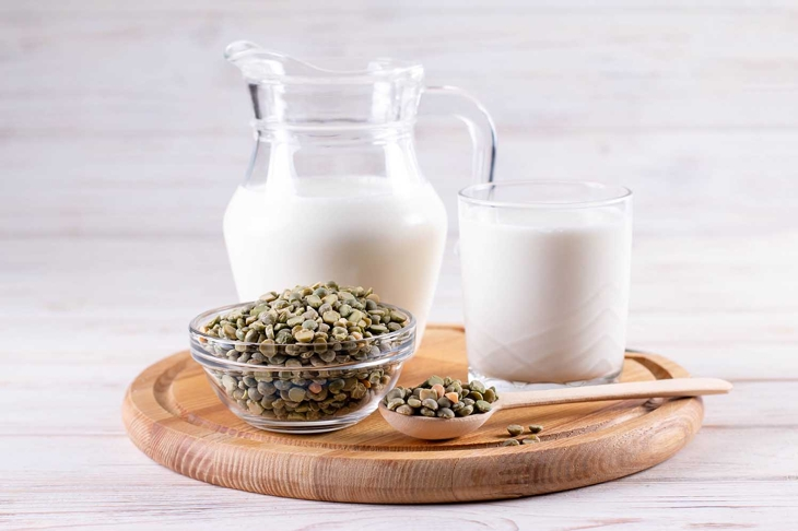 Green peas plant-based milk on a white wooden table. Gluten-free, soy free, lactose-free product
