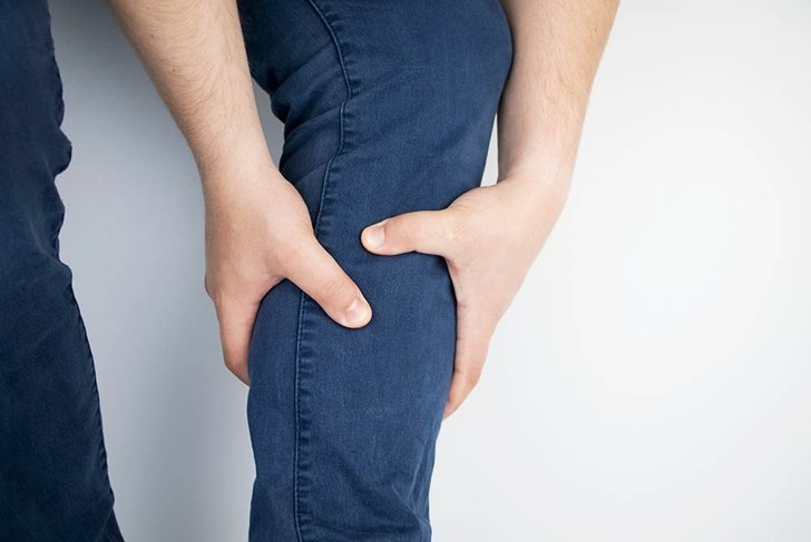 A man suffers from pain in the calves. Stretching the calf muscle, varicose veins, leg cramps, or myositis. Orthopedic doctor examines