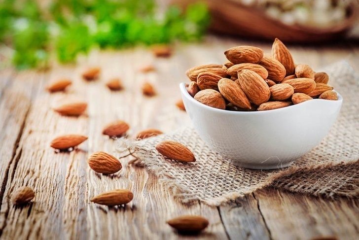 Almonds in white porcelain bowl on wooden table. Almond concept with copyspace.