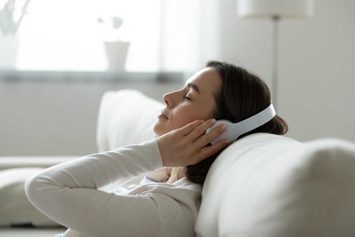 Calm female resting leaned on comfy couch in living room spend free time at home closed eyes enjoy music listening favourite song through wireless modern headphones. Pastime weekend relaxation concept