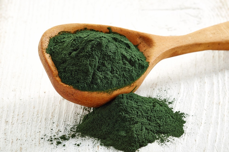 Wooden spoon of spirulina algae powder on white wooden background
