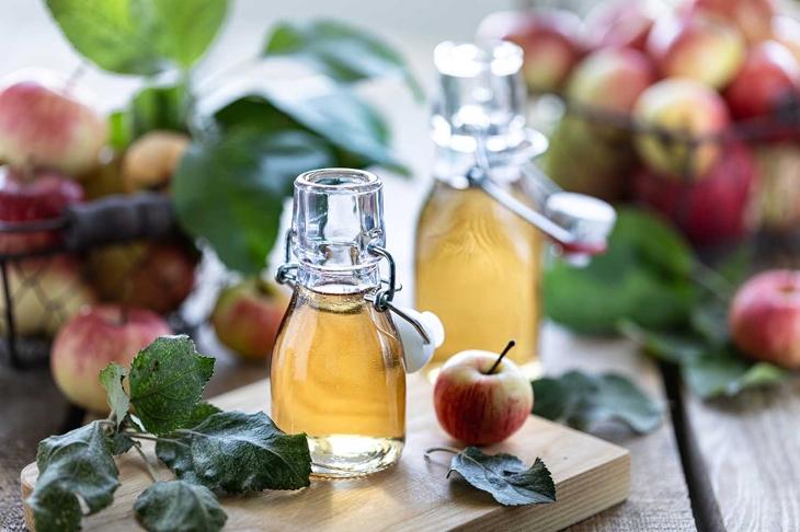 Apple vinegar. Bottle of apple organic vinegar or cider on wooden background. Healthy organic food
