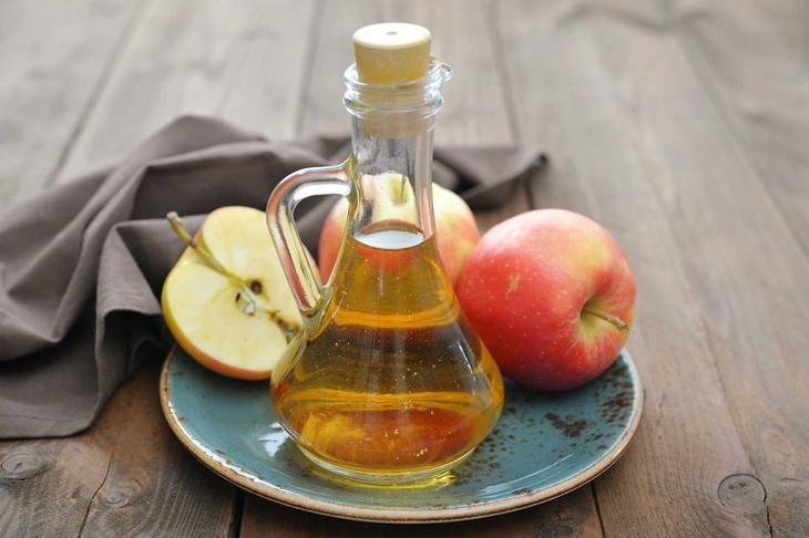 Apple cider vinegar in glass bottle and fresh apples on wooden background