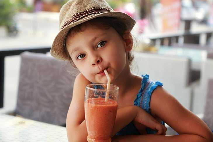 resilient child drinks from orange smoothie after being raised properly