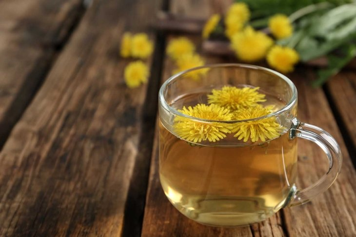 Delicious fresh dandelion tea on wooden table, closeup. Space for text