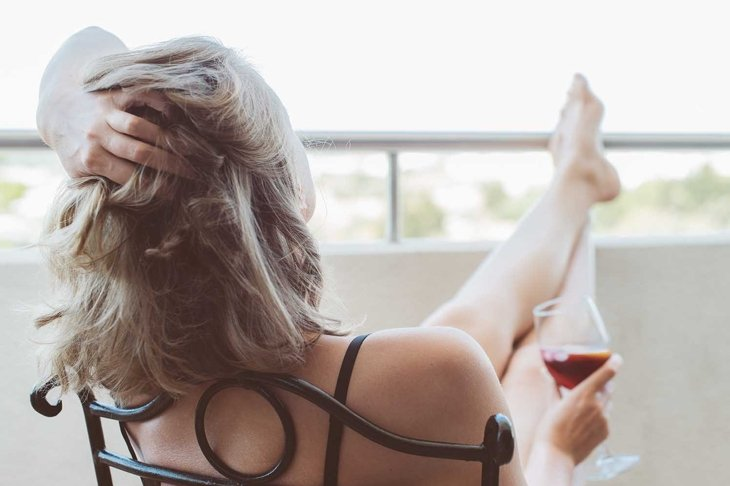 Woman enjoying her red wine on balcony.