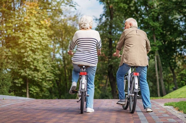 Mature man and woman cycling in nature