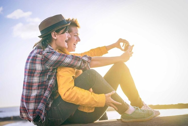 Happy lesbian couple taking a selfie with mobile smart phone camera on the beach at sunset - Vignette edit - Homosexuality, diversity, vacation, travel, lgbt, technology concept