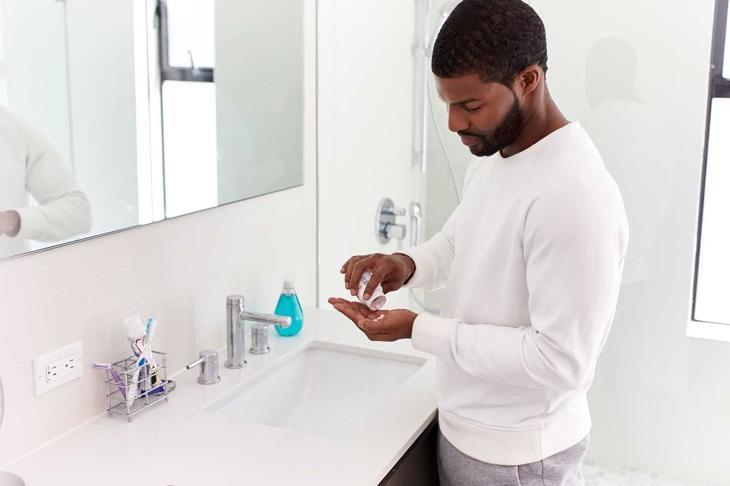 Man In Bathroom Taking Vitamin Supplement Tablets