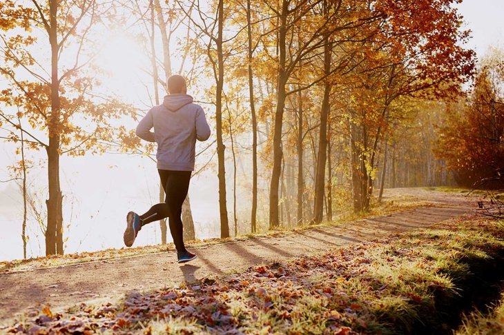 Man running in park at autumn morning. Healthy lifestyle concept