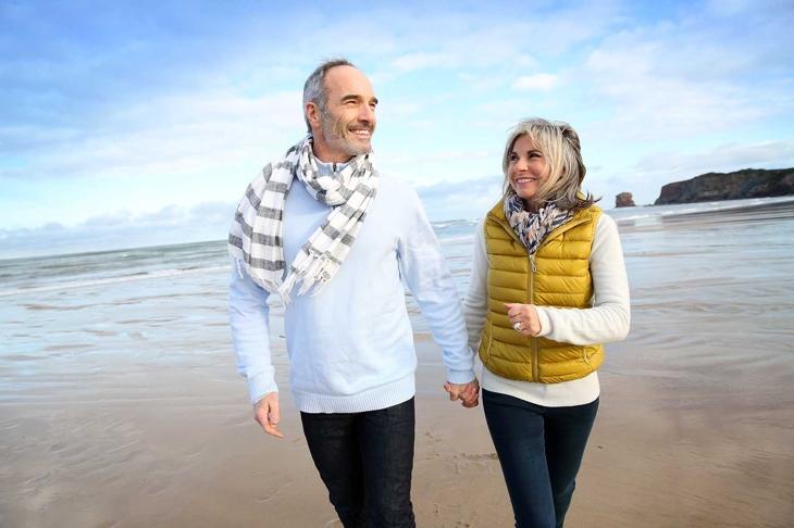 Cheerful senior people walking on the beach